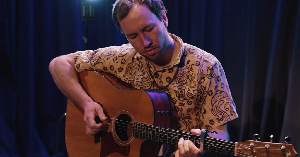 Charles Ostiguy joue de la guitare acoustique d'ambiance